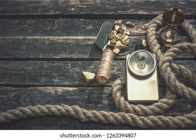 Compas, gold nuggets on the spade, rope and vintage flashlight on the aged wooden table background with copy space. Treasure hunter or goldminer concept.