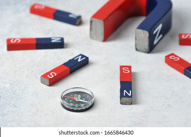 compass among magnets - a large horseshoe magnet and flat magnets attracted to it-magnets with red and blue poles