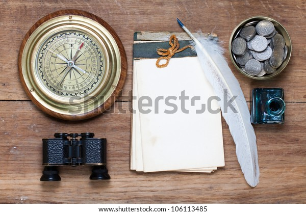 Compass, antique notebook, binoculars, quill and inkwell, coins on wood