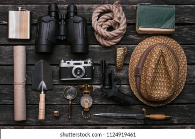 Compass, binoculars, film photo camera, loupe, dagger, handgun, diary book, shovel, rope, gold ore and old scroll document on adventurer or explorer wooden table. Traveler.