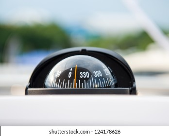 Compass and dashboard instruments of a yacht.