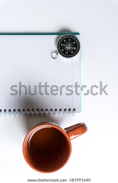 A compass, glass of water and a note writing book isolated over white background. Relax and traveling planning.