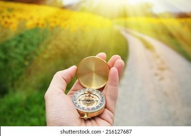 Kompass in der Hand gegen Landstraße