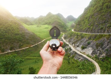 Compass in the hand of the traveler the background of roads in the mountains. North Vietnam.