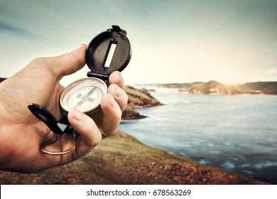 Compass in the hand traveler on the coastline near sea background hills and mountains.