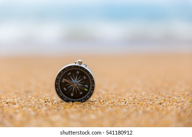 compass lying on the sand on the beach