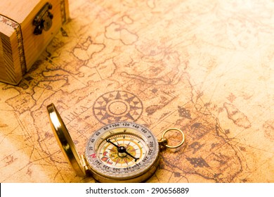 compass lying on vintage map with treasure chest