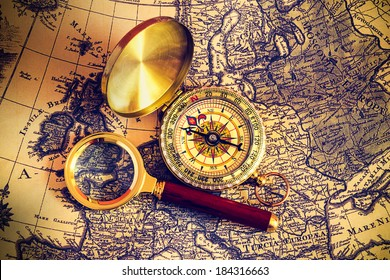 compass and magnifying glass lie on the topographic map