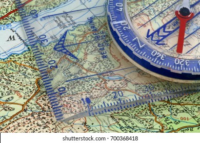 Compass and map – A magnetic compass being lined up on  map grid lines