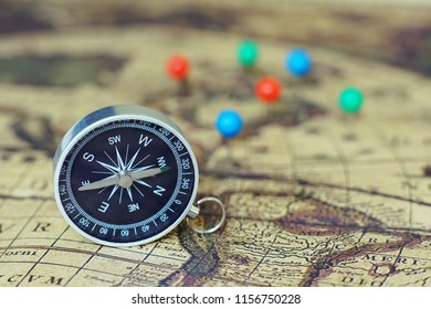 Compass and marking pins on blur vintage world map, journey concept, copy space