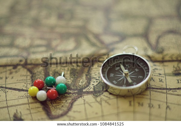 Compass and multi color pins on blur vintage map background
