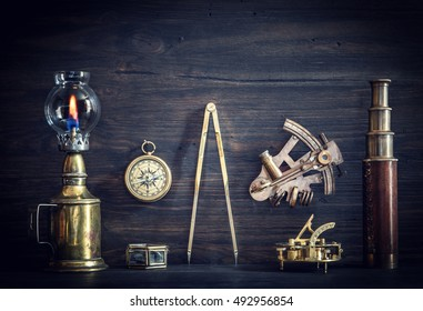 Compass, nautical lamp, sextant, telescope, old coins and a sundial on the captain's Desk. Retro style.