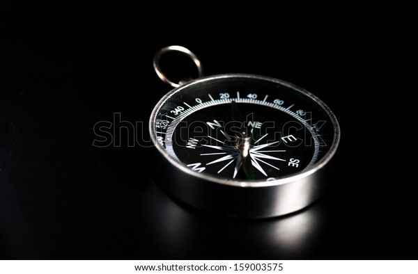 Compass on  black board background and a lot of copy space. Concept - compass showing the right direction in business, finance, self development or spiritual life. Copy space.
