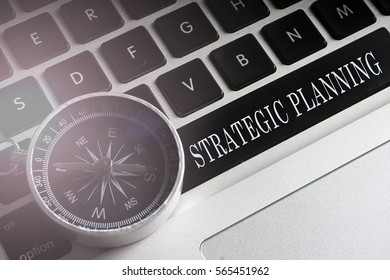 Compass on the black keybord with planning,strategic conceptual text. low light