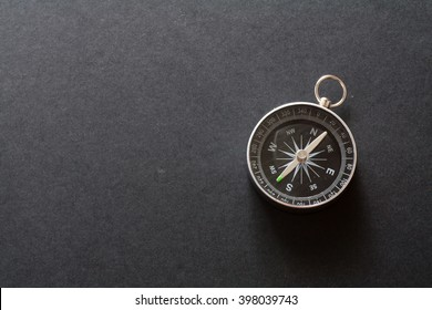 Compass on black paper background