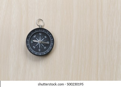 Compass on the brown wooden floor,concept of traveling and trekking.