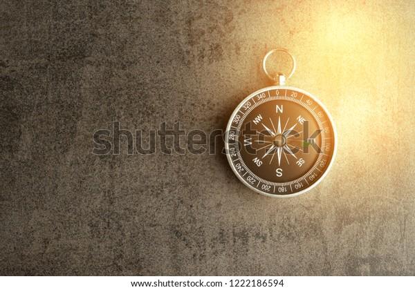 Kompass auf dunkelschwarz strukturierter Tafel mit künstlich goldenem Flair mit Kopienraum als Fahrtrichtung, Reise- oder Abenteuerkonzept.