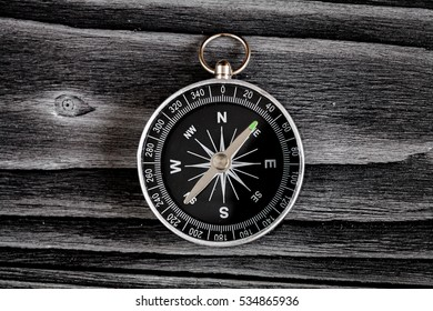 compass on dark wooden background concept direction motion top view