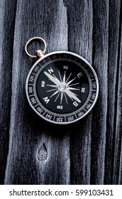 compass on dark wooden background concept direction motion top v