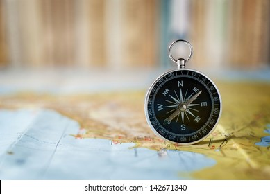 compass on the map and book in the background in the area of confusion