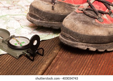 compass on a map with hiking-boots