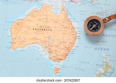 Compass on a map pointing at Australia and planning a travel destination