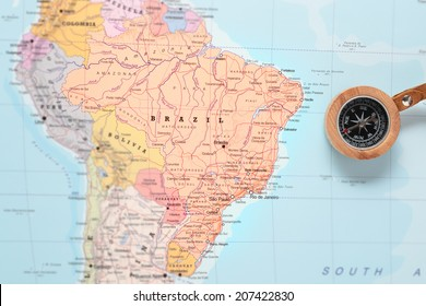 Compass on a map pointing at Brazil and planning a travel destination