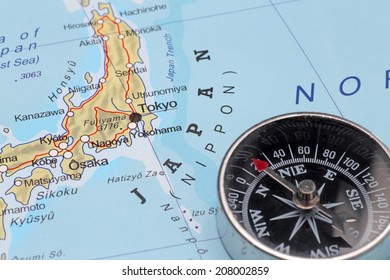 Compass on a map pointing at Japan and planning a travel with destination Tokyo