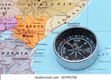 Compass on a map pointing at Kenya and planning a travel destination