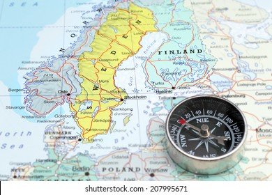 Compass on a map pointing at Norway Sweden and Finland, planning a travel destination in Scandinavia