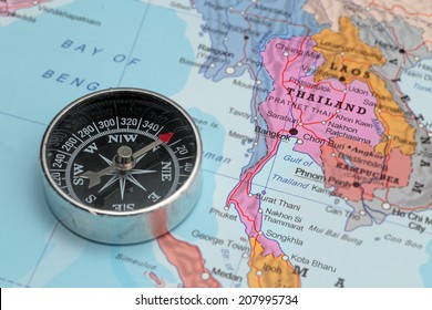 Compass on a map pointing at Thailand and planning a travel destination