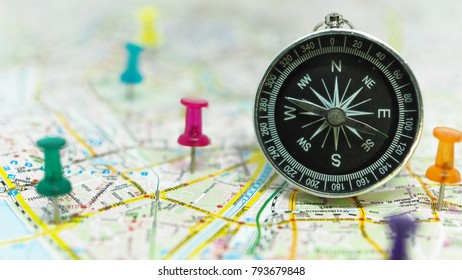 Compass on map for tourism and exploration, focus on compass
