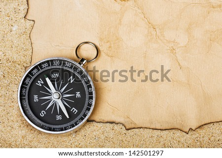 Compass on old paper against the background of sand