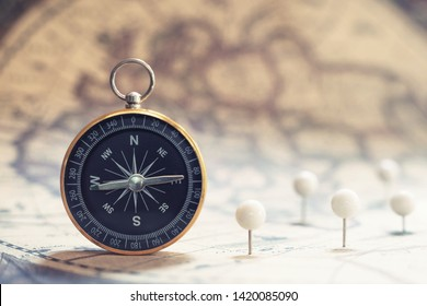 Compass on old vintage brown map background, journey planning concept, copy space