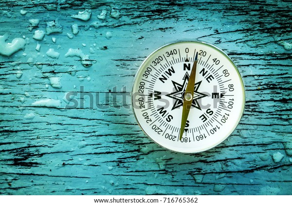 compass on old wood table with water drops, find the right direction concept, flat top view