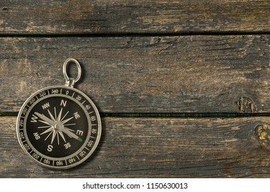 Compass on an old wooden background. Adventure and travel concept. Copy space