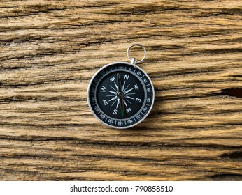 Compass on old wooden background
