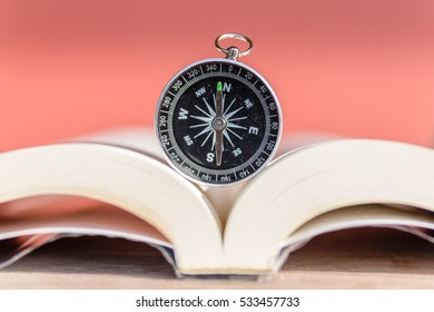 Compass on open old book