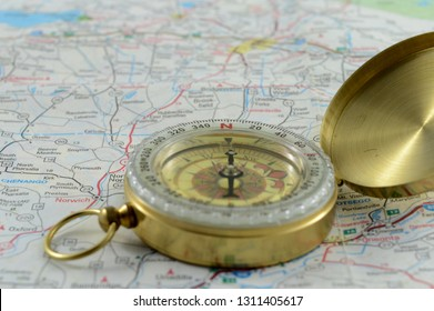 Compass on top of a map for navigational directions.