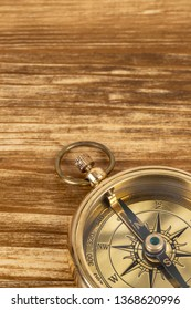 Compass on wooden background, concept for direction transportation and travel, with copy space