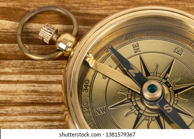 Compass on wooden background, concept for direction transportation and travel