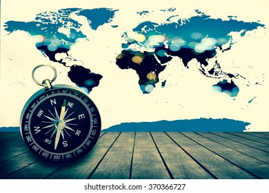 compass on wooden floor with world map on blur bokeh light in city background