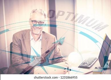Compass with optimum text against portrait of businessman smiling