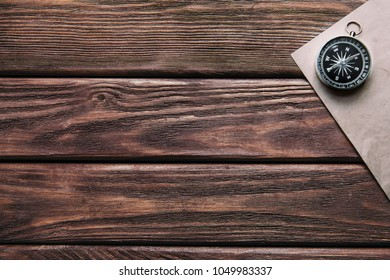 Compass and paper on a wooden background, top view. Copy-space in left part of the image.