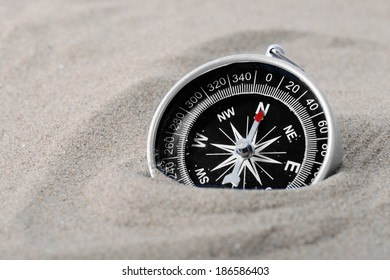 a compass part buried in sand with needle pointing north