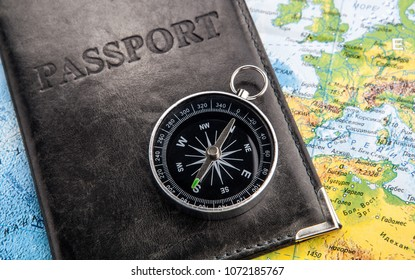 compass passport in cover and world map closeup