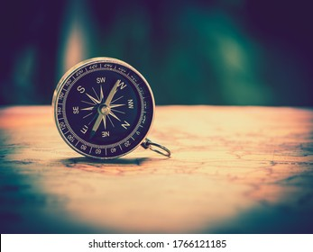 The compass is placed on the ancient or vintage world map . Travel geography navigation concept background.