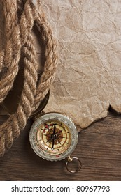 Compass with a rope on the background of the old board
