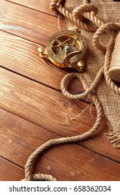 compass and rope on old wooden boards