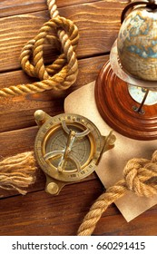 Compass and rope on wooden table. close up